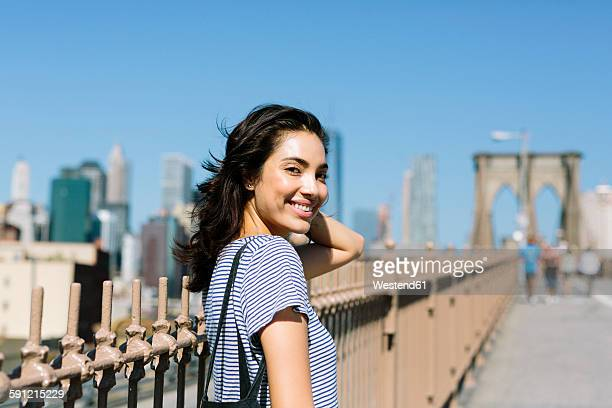 USA, New York City, portrait of smiling young woman on Brooklyn Bridge