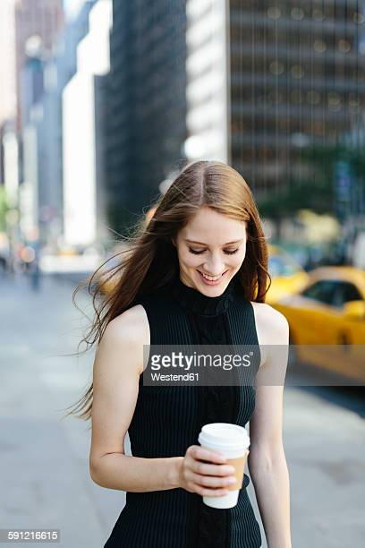 USA, New York City, portrait of smiling young woman with coffee to go