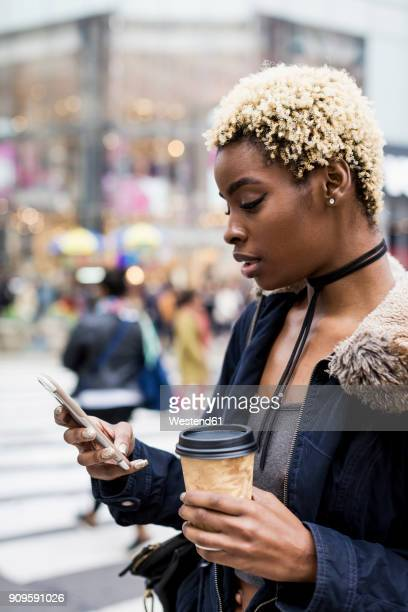 USA, New York City, portrait of young woman with coffee to go