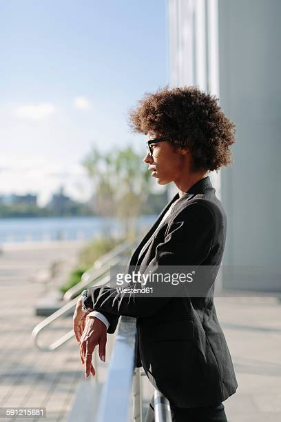 usa, new york city, profile of businesswoman leaning on railing - black jacket stock photos and pictures