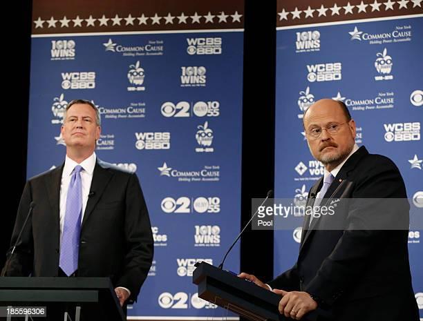 New York City Republican mayoral candidate Joe Lhota right glances at a screen as New York City Democratic mayoral candidate Bill de Blasio looks...