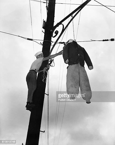A New York City resident adjusts the hanging effigy of the enemy on Victory over Japan Day 1945