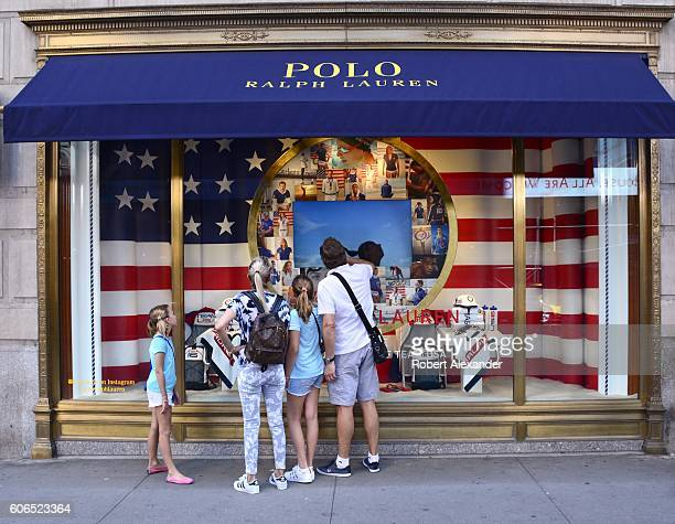 August 27, 2016: New York City shoppers and visitors pause on their walk along Fifth Avenue to admire the window display at the Polo Ralph Lauren...