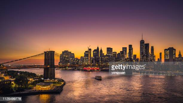 skyline von new york und brooklyn bridge bei sonnenuntergang - new york city stock-fotos und bilder