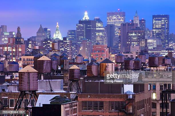 USA, New York City skyline and water towers on roofs, dusk