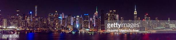 New York city skyline at night time, displaying colorful lights on its skyscraper.