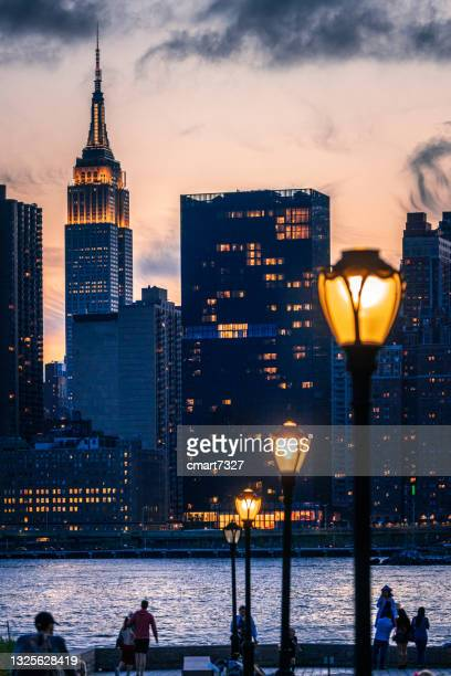 new york city skyline with lanterns and new yorkers in the foreground - queens new york city stock pictures, royalty-free photos & images