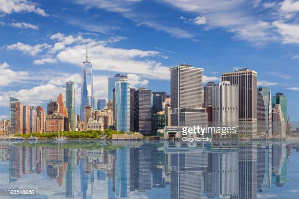 new york city skyline met manhattan financial district en world trade center weerspiegeld in water van new york harbor, ny, usa. - stad new york stockfoto's en -beelden