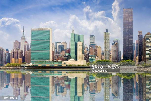 new york city skyline with midtown manhattan skyscrapers, un building and empire state building reflected in water of east river, ny, usa. - united nations building stock pictures, royalty-free photos & images