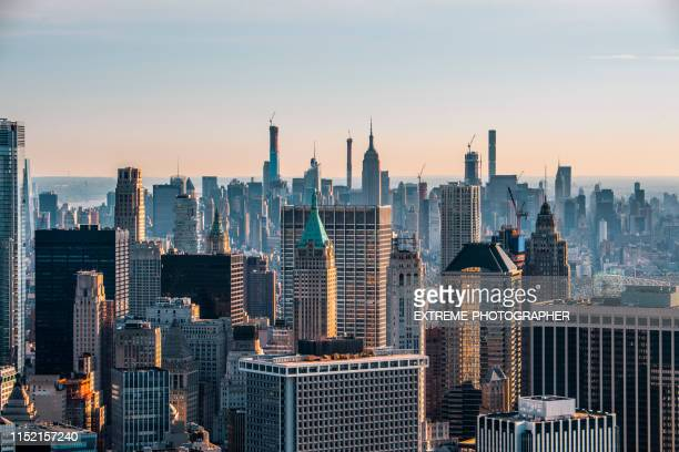 new york city skyline with the trump tower in lower manhattan, taken from a helicopter flying above rooftops at sunrise - wall street lower manhattan stock pictures, royalty-free photos & images