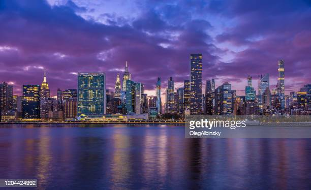 new york city skyline with un building, chrysler building, empire state building and east river at sunset. - midtown manhattan stock pictures, royalty-free photos & images
