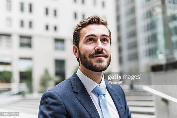 USA, New York City, smiling businessman looking up