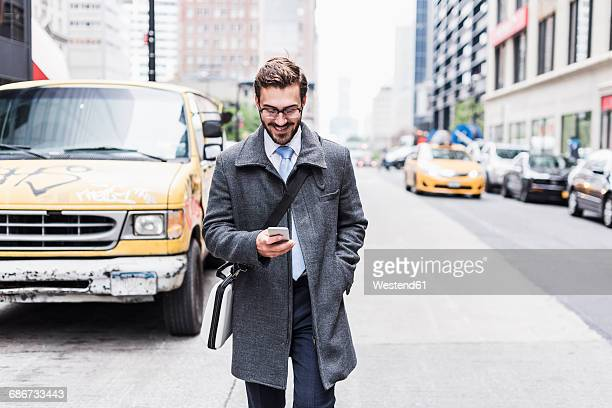 usa, new york city, smiling businessman with cell phone on the go - coat stock-fotos und bilder