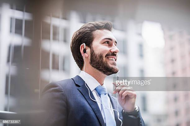 USA, New York City, smiling businessman with earphones