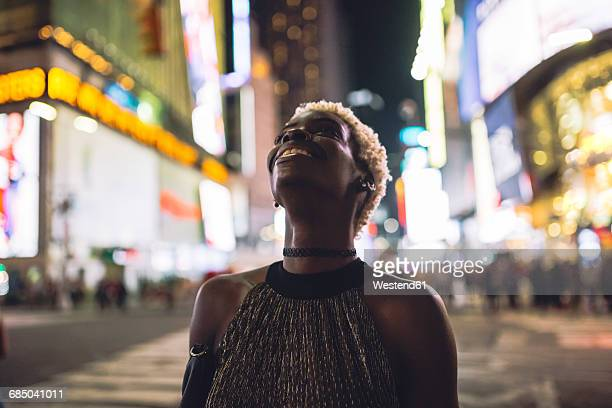 usa, new york city, smiling young woman on times square at night looking up - times square manhattan stock pictures, royalty-free photos & images