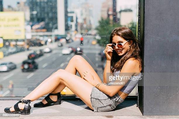 USA, New York City, smiling young woman relaxing in the city