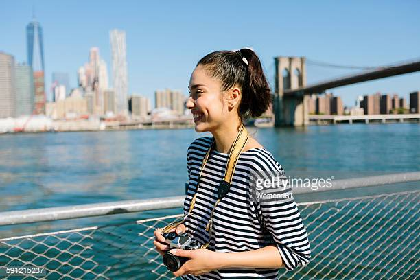 USA, New York City, smiling young woman with camera