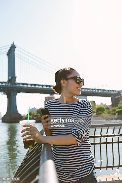 USA, New York City, smiling young woman with soft drink looking at smartphone
