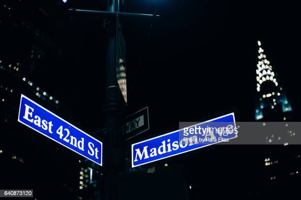 New York City street signs and Chrysler building in the background at night
