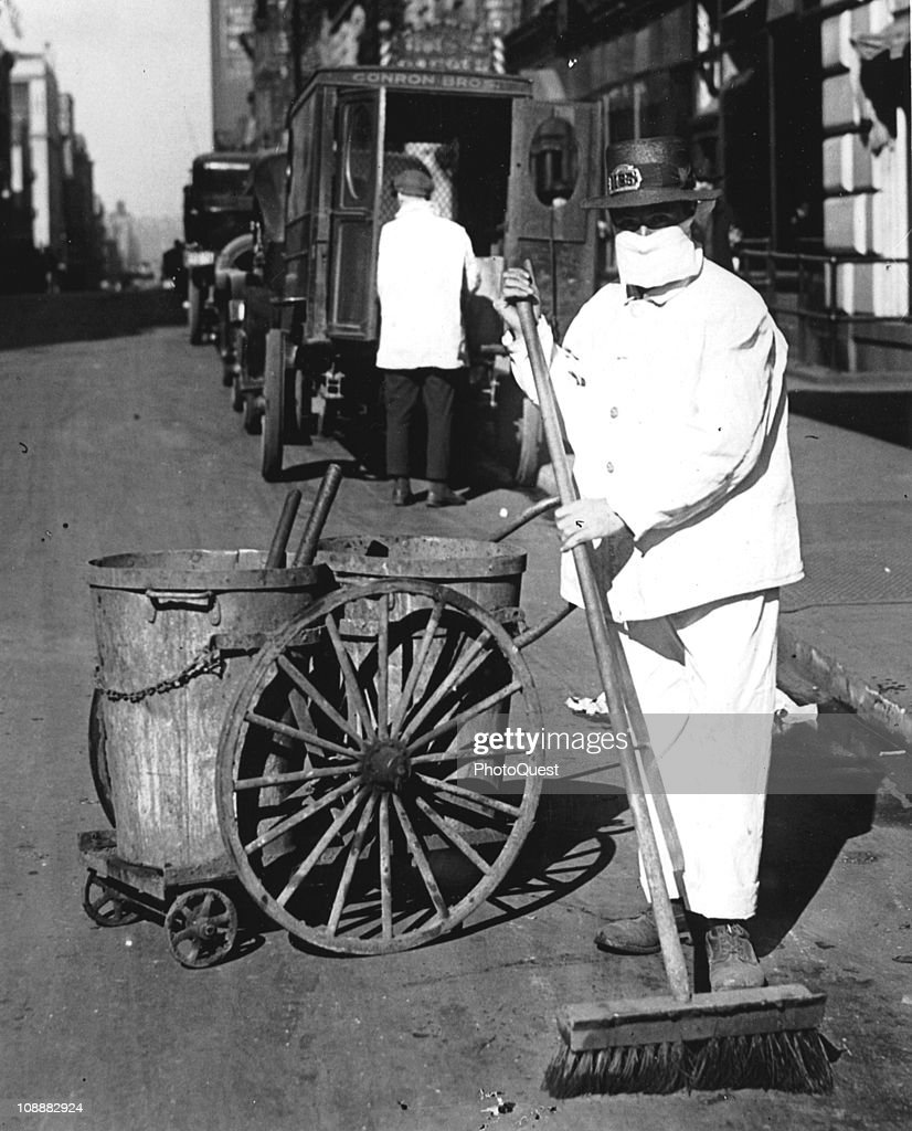 A New York city street sweeper wears a mask to help check the spread of the influenza epidemic, October 1918. In the view of one official of the New York Health Board, it is 'Better be ridiculous, than dead'.