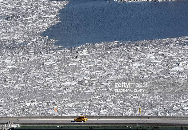 A New York City Taxi drives up the FDR Drive alongside and ice filled East River in New York February 24 2015 Heavy ice in the East River shut down...