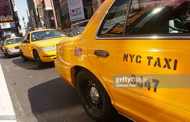 New York City taxis wait for passengers in Times Square October 10 2001 in New York Taxi drivers have seen their incomes drop significantly since the...