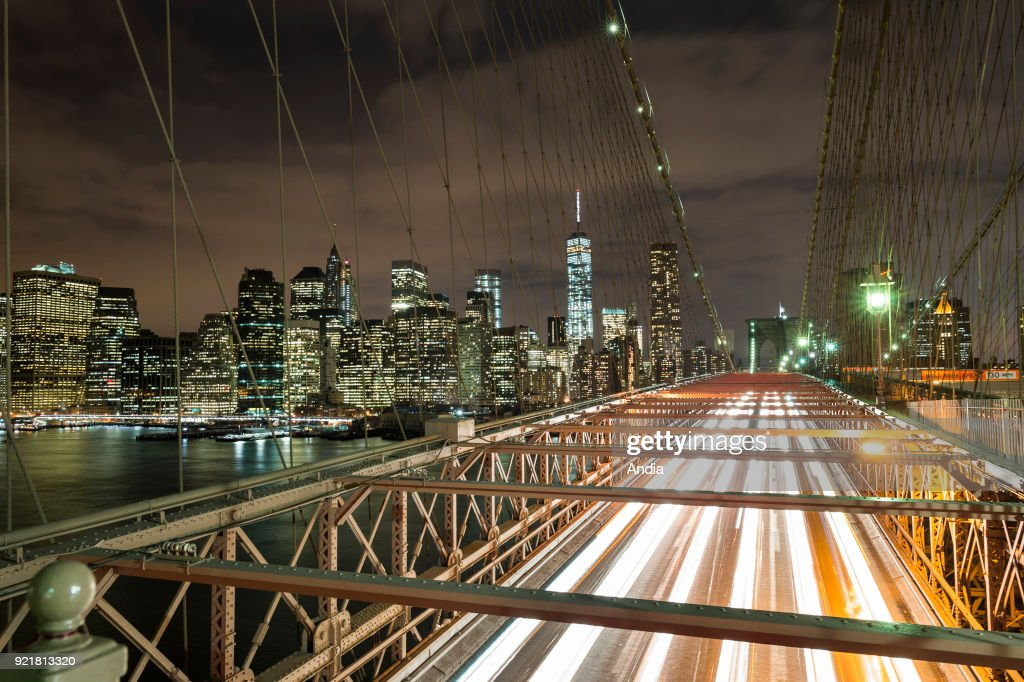 the city lit up at night and the Brooklyn Bridge, East River, between Brooklyn and Manhattan.