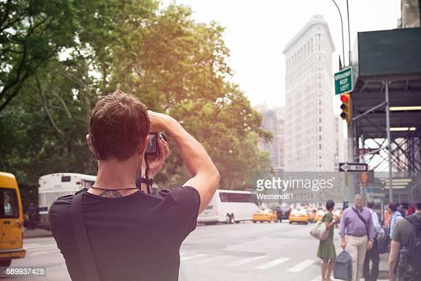 USA, New York City, Tourist taking pictures of Flatiron Building