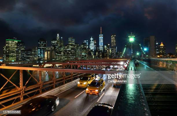new york city traffic in the brooklyn bridge and manhattan skyline at night - carlos alkmin stock pictures, royalty-free photos & images