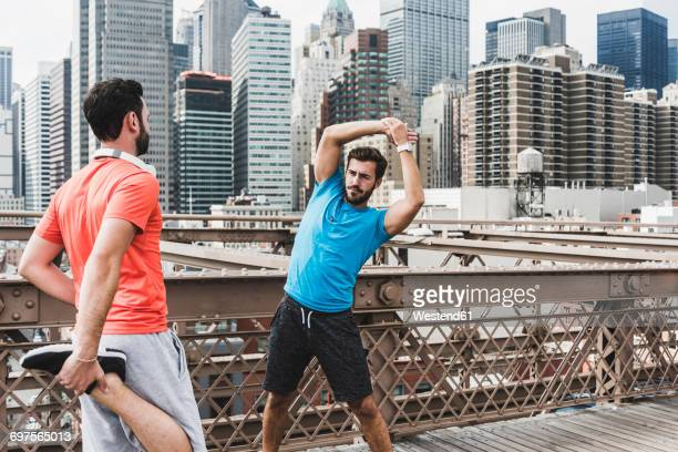 USA, New York City, two athletes stretching on Brooklyn Brige