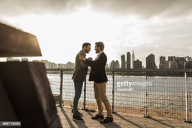 USA, New York City, two businessmen meeting at East River
