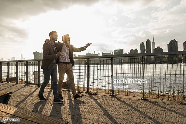 USA, New York City, two businessmen walking together along East River
