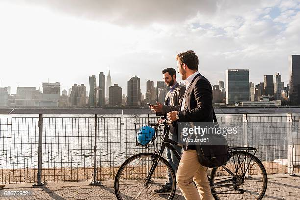 USA, New York City, two businessmen with bicycle walking along East River