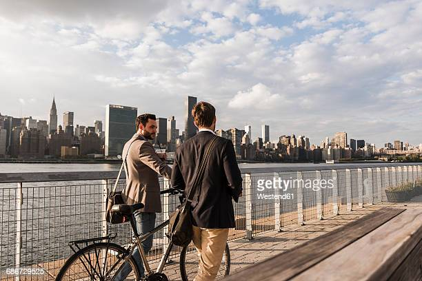 usa, new york city, two businessmen with bicycle walking along east river - gemeinsam gehen stock-fotos und bilder
