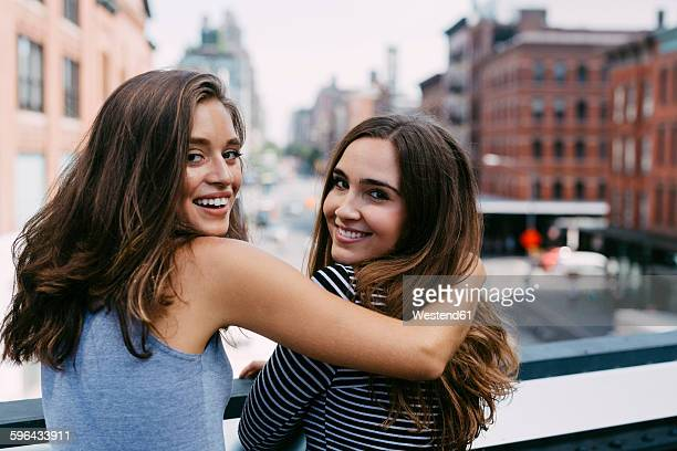 USA, New York City, two friends embracing in the city