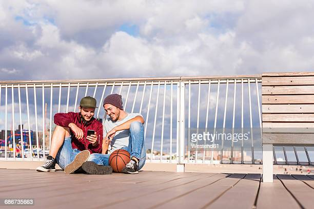 USA, New York City, two friends sitting on bridge on Coney Island sharing cell phone