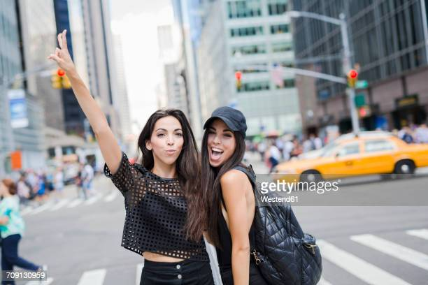 USA, New York City, two happy fashionable twin sisters in Manhattan