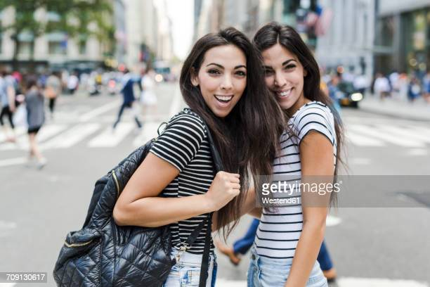 USA, New York City, two happy twin sisters in Manhattan