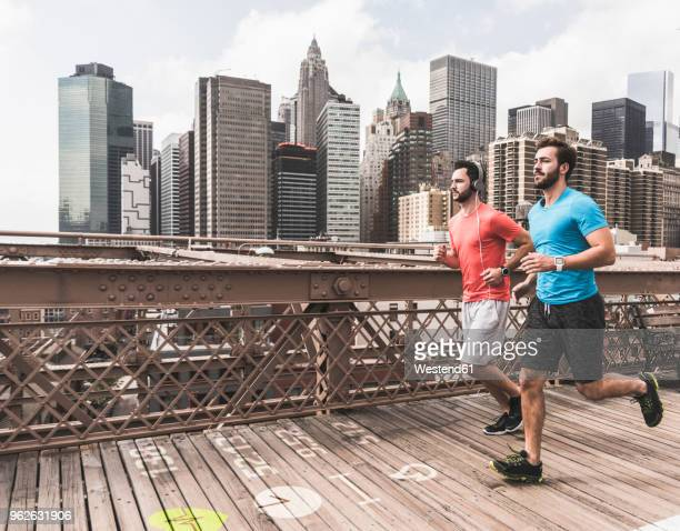 USA, New York City, two men running on Brooklyn Brige with data on the ground