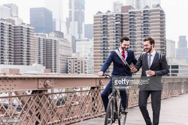 USA, New York City, two smiling businessmen on Brooklyn Bridge