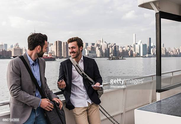 USA, New York City, two smiling businessmen talking on ferry on East River