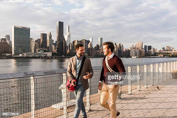 USA, New York City, two young men walking along East River