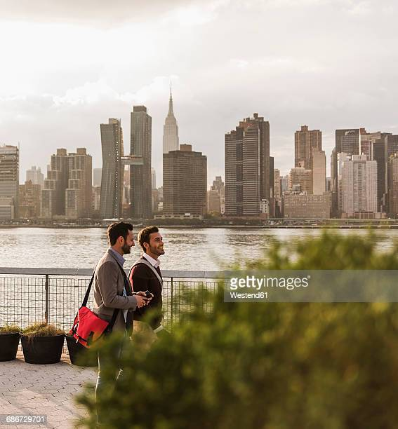 usa, new york city, two young men walking along east river - gemeinsam gehen stock-fotos und bilder