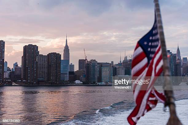 USA, New York City, US flag on ferry on East River with skyline of Manhattan in background