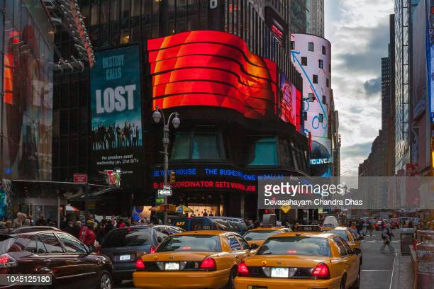 new york city, usa - looking up 7th avenue from time square at almost sunset time; there is heavy traffic on the street. brightly coloured advertisement typical of the area, is seen in the image. - 7th avenue stock pictures, royalty-free photos & images