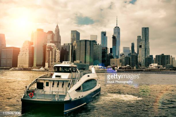new york city water taxi on the east river, with the skyline of lower manhattan in the background. new york city, usa - schiffstaxi stock-fotos und bilder