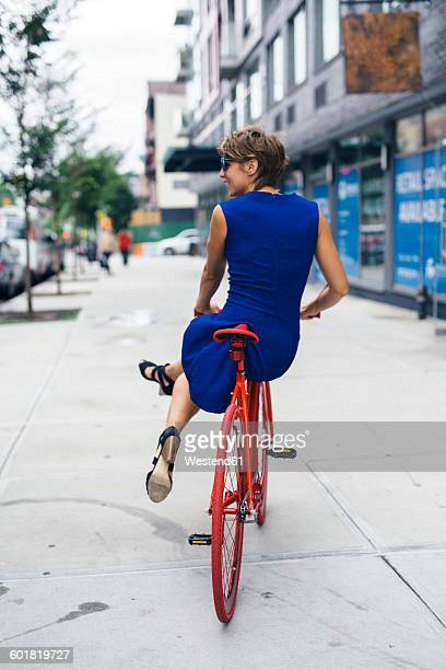 USA, New York City, Williamsburg, back view of smiling blond woman balancing on red bicycle