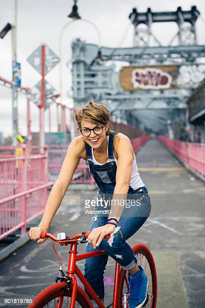 USA, New York City, Williamsburg, portrait of blond woman with red racing cycle on Williamsburg Bridge