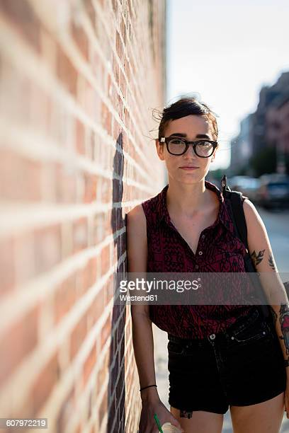 USA, New York City, Williamsburg, portrait of young woman leaning against brick wall