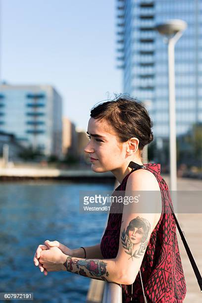 USA, New York City, Williamsburg, tattooed young woman leaning on a railing